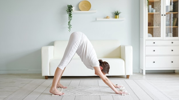 Pretty young pregnant woman does adho mukha svanasana practicing yoga pose on floor mat near sofa in spacious room at home side view