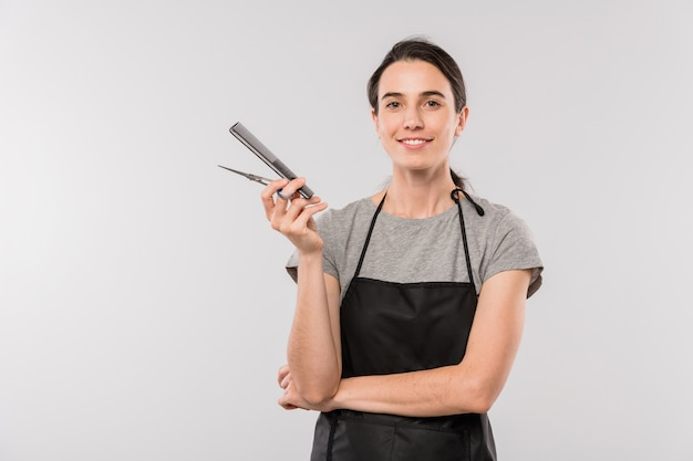 Довольно молодой профессиональный женский парикмахер с расческой и ножницами смотрит на вас изолированно