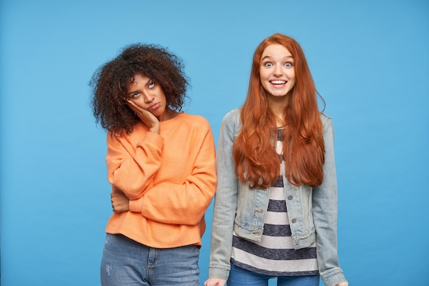 Pretty young puzzled brown haired dark skinned woman holding palm on her cheek while looking upwards with bored face, standing over blue wall with joyful redhead female