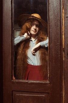 木製のドアの後ろに麦わら帽子のかなり若い赤い髪のモデル