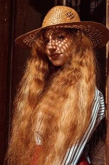 彼女の顔に影のある麦わら帽子のかなり若い赤い髪のモデル