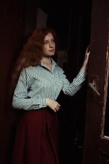 오래 된 문 뒤에 서 있는 줄무늬 셔츠와 빨간 치마에 꽤 젊은 빨간 머리 모델