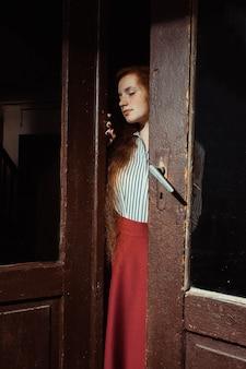 古い木製のドアを開く長い巻き毛のかなり若い赤い髪のモデル