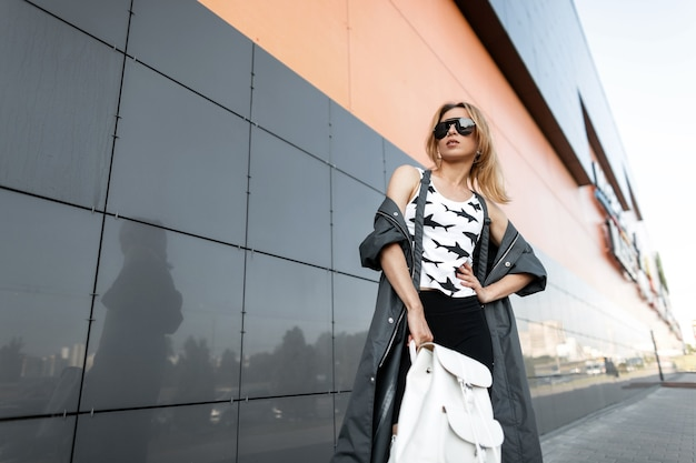 최신 유행의 옷을 입고 유행 선글라스에 꽤 젊은 빨간 머리 여자는 현대적인 건물 근처 도시에서 포즈. 여름 날에 산책에 미국 여자 패션 모델. 스트리트 스타일.