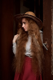 Pretty young red haired woman with freckles in straw hat posing near old door