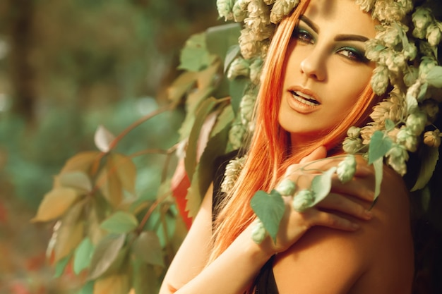 森の中で屋外ホップでポーズをとるかなり若い赤毛の女性