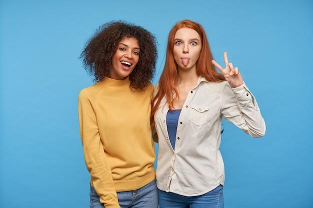 Довольно молодая рыжая дама корчит рожи и показывает язык, поднимает руку со знаком мира, позируя над синей стеной с радостной темнокожей кудрявой женщиной