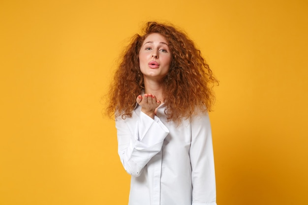 Pretty young redhead woman girl in casual white shirt posing isolated on yellow orange wall