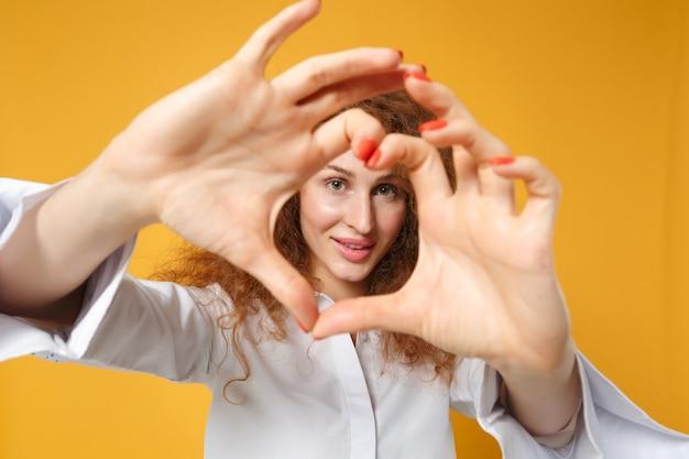 黄色いオレンジ色の壁に分離されたポーズをとってカジュアルな白いシャツを着たかなり若い赤毛の女性の女の子