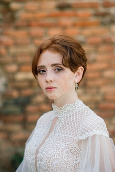 Pretty young redhead woman outside with her wedding dress