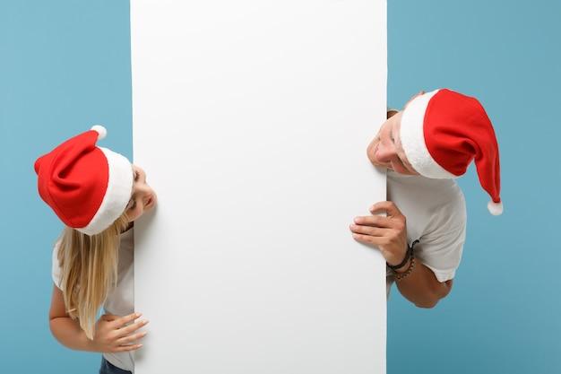クリスマスの帽子をかぶったかなり若いサンタカップルの友達の男と女