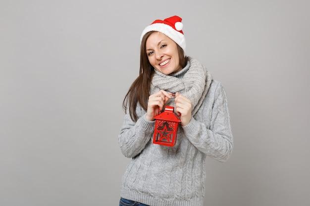 灰色のセーター、灰色の背景に分離されたヴィンテージのランタン燭台を保持しているスカーフクリスマス帽子のかなり若いサンタの女の子。明けましておめでとうございます2019お祝いホリデーパーティーのコンセプト。コピースペースをモックアップします。