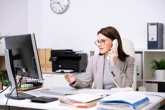 Довольно молодая секретарша сидит за столом перед монитором компьютера, обсуждая данные с клиентом по телефону
