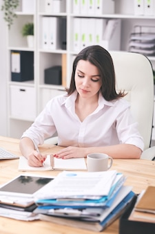 机のそばの肘掛け椅子に座って、棚の背景にノートブックで作業計画を立てる白いシャツを着たかなり若い真面目な女性