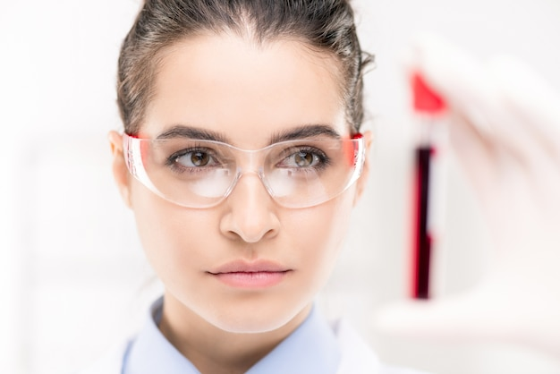 Pretty young serious female looking through protective eyeglasses at flask with sample of new vaccine developed in laboratory