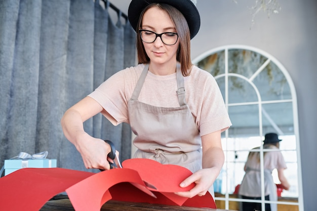 Pretty young serious woman in workwear cutting large red paper heart while working in studio