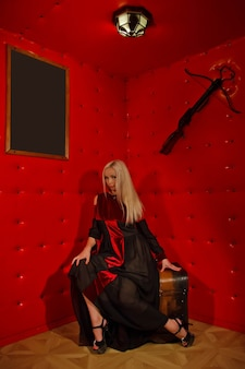 Pretty young sexy blonde in gothic dress in interior of medieval red torture room sits on chest against textured wall. image of halloween horror queen. copy space for text or logo
