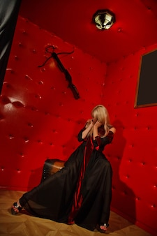 Pretty young sexy blonde in gothic dress in interior of medieval red torture room