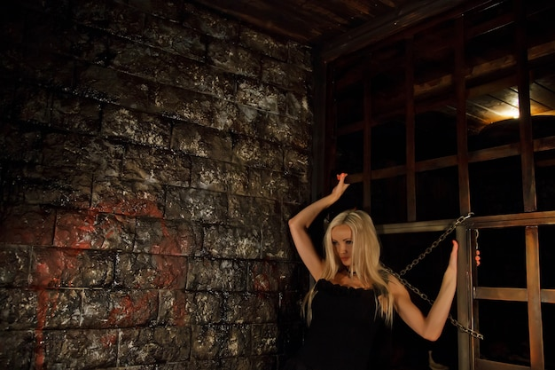 Pretty young sexy blonde woman in black attire in interior of medieval dark room with cages and chains on background of an old texture wall. image of queen of halloween horror night. copy space