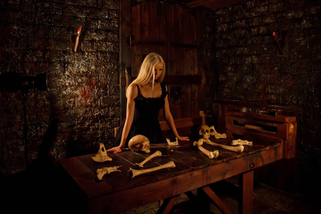 Pretty young sexy blonde woman in black attire in interior of medieval dark room with table with skull and bones on background of an old texture wall. image of queen of halloween horror. copy space