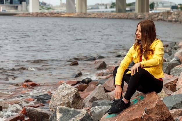 Довольно молодая сексуальная женщина спортивного телосложения сидит на камне на городском пляже