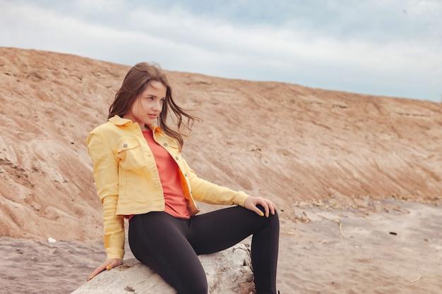 도시의 해변을 걷고 있는 밝은 옷을 입은 운동 선수의 꽤 젊은 섹시한 여자. 도시 바다 해변에서 산책. 자연에 노란색 재킷과 검은색 바지를 입은 귀여운 예쁜 여성의 초상화