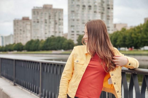 도시의 운하 제방을 걷는 밝은 옷을 입은 운동 선수의 꽤 젊은 섹시한 여자. 도심에서 도보. 거리에 노란색 재킷과 검은색 바지를 입은 귀여운 예쁜 여성의 초상화