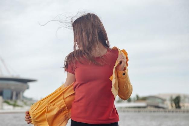 도시의 해안선을 걷고 있는 밝은 옷을 입은 운동 선수의 꽤 젊은 섹시한 여자. 도시 바다 해변에서 산책. 바다 해안에 노란색 재킷과 검은 바지에 귀여운 예쁜 여성의 초상화