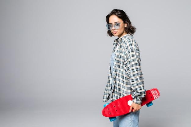 Девушка довольно молодая фигуристка держит скейтборд изолированы