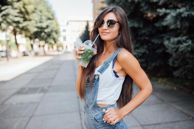 Довольно молодая стройная женщина в солнечных очках и рубашке в городе выпивает свежий напиток