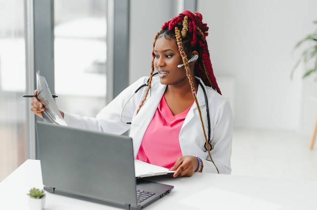 웹캠으로 온라인 건강 관리 조언을 제공하는 꽤 젊은 똑똑한 여성 의사 또는 치료사