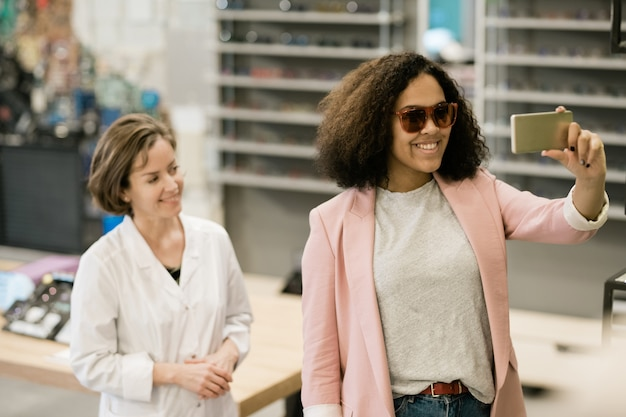 Довольно молодой улыбающийся клиент магазина оптики примеряет новые солнцезащитные очки и делает селфи с консультантом