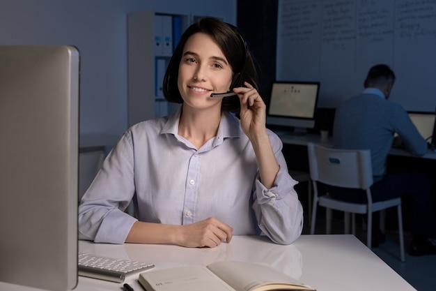 オフィスでオンラインでクライアントに話しかけるヘッドセットを持つかなり若い笑顔のカスタマーサポート担当者