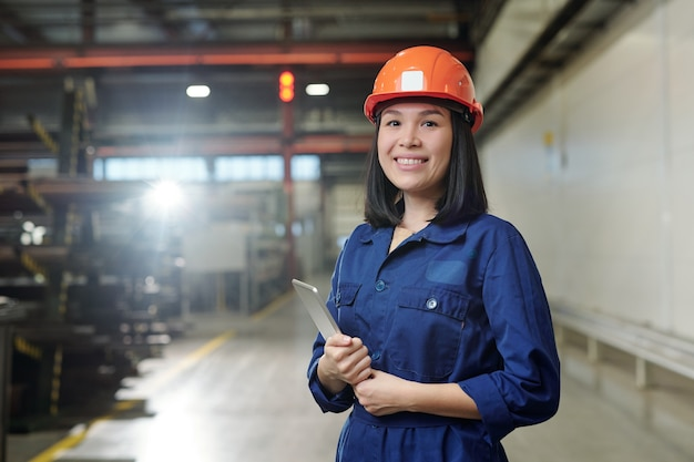 Pretty young smiling engineer in uniform and protective helmet holding tablet while posing
