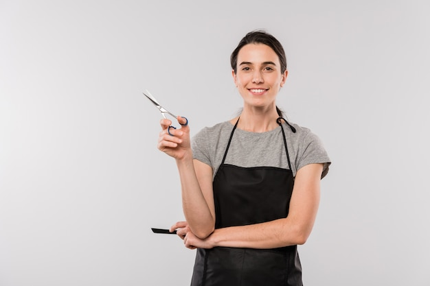 Довольно молодая улыбающаяся женщина-парикмахер с расческой и ножницами смотрит на вас изолированно