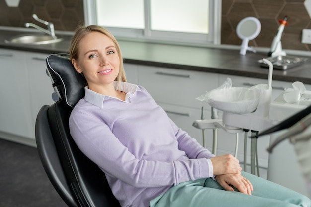 Pretty young smiling female patient of contemporary dentistry sitting in leather armchair and waiting for her doctor in clinics