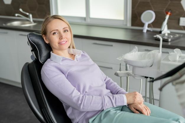Довольно молодая улыбающаяся пациентка современной стоматологии сидит в кожаном кресле и ждет своего врача в клиниках
