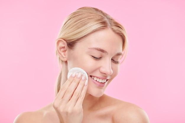 Довольно молодая улыбающаяся женщина с ватным диском наслаждается процедурой очистки лица тонером или мицеллярной водой