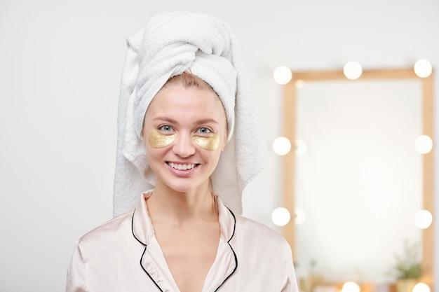 シャワーの後のバスルームで目の下のマスクを持っている頭にタオルでかなり若い笑顔の女性