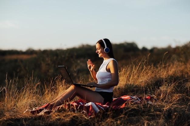 ビデオ通話にラップトップとワイヤレスイヤホンを使用しながら、夏の晴れた日に公園の芝生に座っているかなり若い笑顔の女の子。
