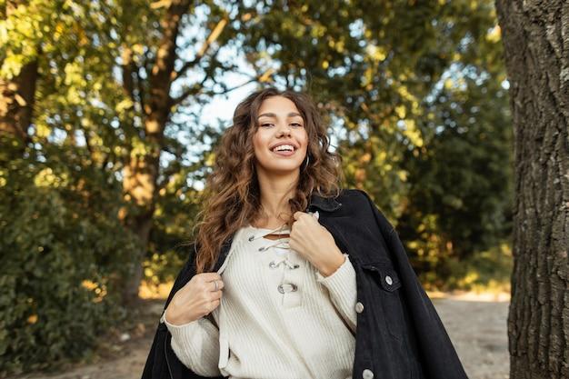 유행 데님 재킷과 니트 블라우스에 곱슬 머리를 가진 꽤 젊은 웃는 소녀는 자연에서 산책. 행복한 여성의 얼굴