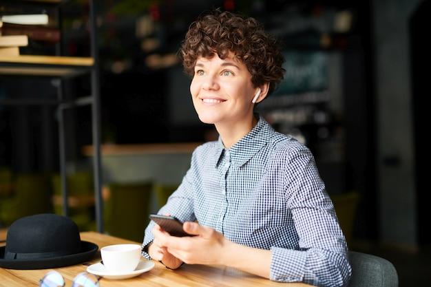 カフェのテーブルのそばに座って、お茶とメッセージングを持つ暗い巻き毛のかなり若い笑顔の女の子