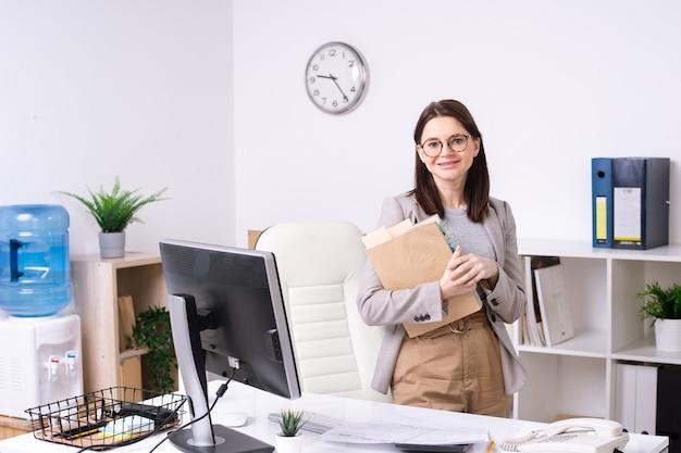 コンピューターで職場のそばに立っている間あなたを見ているドキュメントを持つかなり若い笑顔のオフィスマネージャーまたは会計士