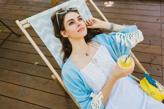 Pretty young smiling stylish woman sitting in deck chair in summer outfit, wearing white dress, blue cape, sunglasses, purse, drinking fresh juice, relaxing