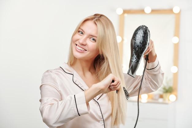 세척 후 그녀의 긴 두꺼운 건강한 금발 머리를 칫솔질하는 동안 헤어 드라이어를 사용하여 잠옷에 꽤 젊은 웃는 여자