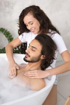 Довольно молодая улыбающаяся женщина делает массаж груди своему мужу, расслабляющемуся в ванне с горячей водой и пеной