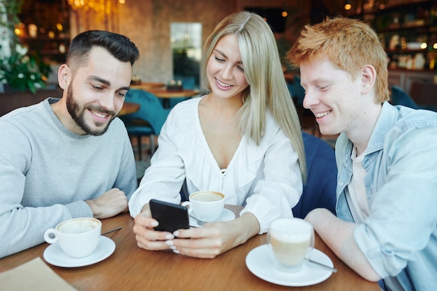 Pretty young smiling woman and two happy guys watching video or images in smartphone while relaxing by cup of coffee in cafe