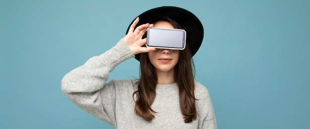 Довольно молодая улыбающаяся женщина в черной шляпе и сером свитере держит телефон, глядя в камеру