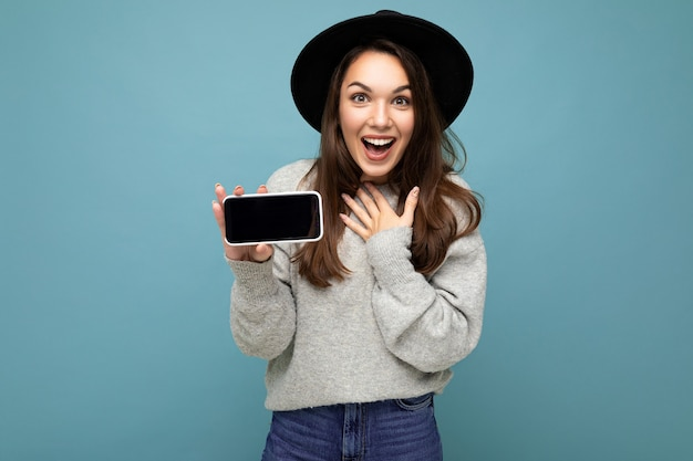 Pretty young smiling woman wearing black hat and grey sweater holding phone looking at camera isolated on background.