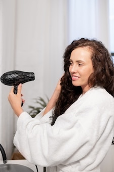 Pretty young smiling woman with hair-dryer taking care of her dark long wavy hair after washing it in bathroom